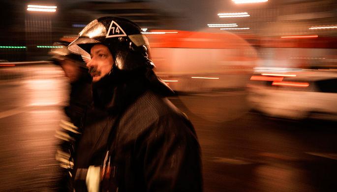 Сотрудники пожарно-спасательных подразделений МЧС на месте пожара в швейном цеху по производству...