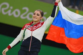 Алия Мустафина, завоевавшая золотую медаль в упражнениях на брусьях на соревнованиях по спортивной гимнастике среди женщин на XXXI летних Олимпийских играх, на церемонии награждения