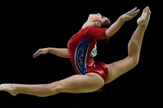 Алия Мустафина выполняет упражнения на бревне в командном многоборье среди женщин на соревнованиях по спортивной гимнастике на XXXI летних Олимпийских играх