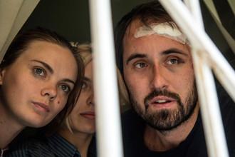Активистки FEMEN и фотограф Дмитрий Костюков выглядывают из окна суда в Киеве