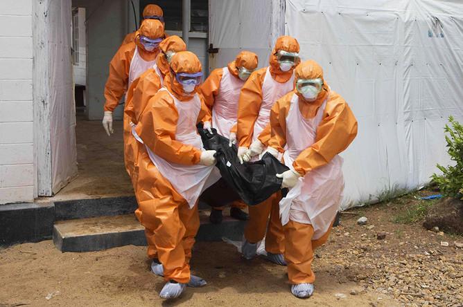 Похоронная команда в защитных костюмах выносит тело умершего из изолятора в окружном госпитале Порт-Локо, Сьерра-Леоне