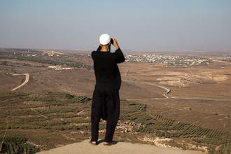 Друз смотрит со стороны Голанских высот на бои между лояльными Башару Асаду войсками и повстанцами