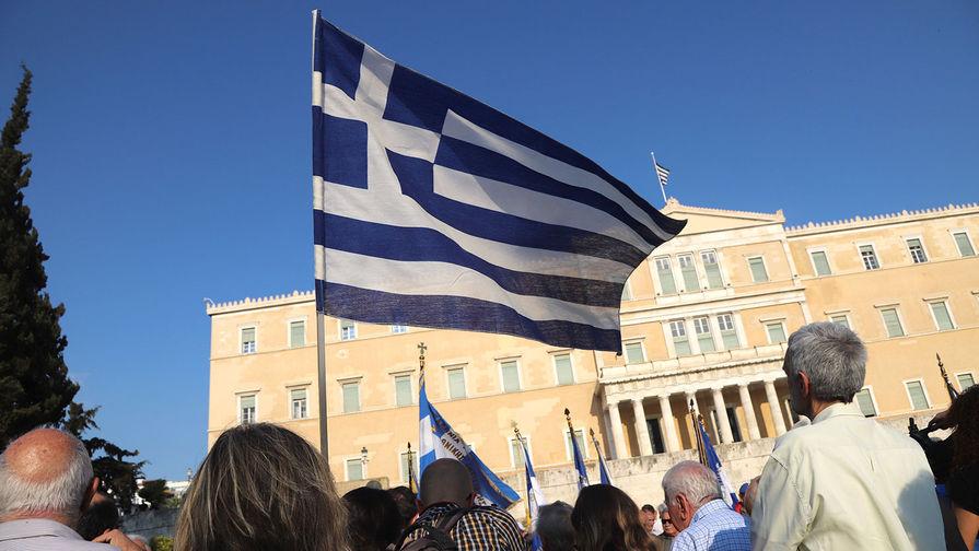 Демонстранты с флагом Греции у здания парламента требуют перейти к переговорам по вопросу о репарациях за ущерб, нанесенный стране нацистской Германией, а также в годы Первой мировой войны. Афины, 27 апреля 2018 года