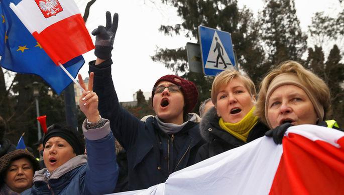 Демонстранты с польскими и европейскими флагами во время митинга около здания парламента в Варшаве, декабрь 2016 года