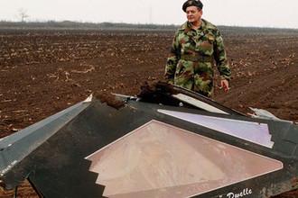 Югославский военный около обломков кабины американского бомбардировщика F-117 под Буджановцами в Сербии, 28 марта 1999 года