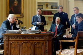 Президент США Дональд Трамп (слева направо) в присутствии главы аппарата Белого дома Райнса Прибуса, вице-президента Майка Пенса, старшего советника Стива Бэннона, директора по связям с общественностью Шона Спайсера и советника по национальной безопасности Майкла Флинна говорит по телефону с президентом России Владимиром Путиным в Овальном кабинете Белого дома в Вашингтоне, 28 января 2017 года