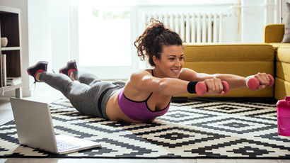 Young woman exercising at home in a living room.