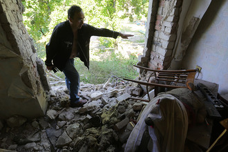 Местный житель в квартире жилого дома, пострадавшей в результате ночного обстрела Горловки