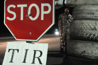 Украинский активист стоит на блокпосту возле Львова, блокируя движение грузовиков с российскими номерами
