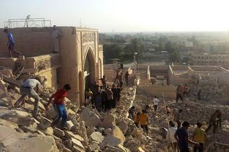 Люди ходят по развалинам разрушенной мечети в Мосуле