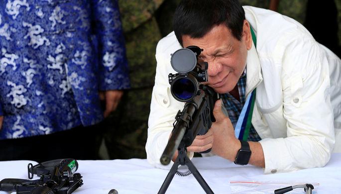 Президент Филиппин Родриго Дутерте со снайперской винтовкой во время церемонии после получения...