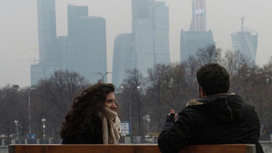 Молодые люди в парке на Воробьевых горах на фоне Московского международного делового центра «Москва-Сити»