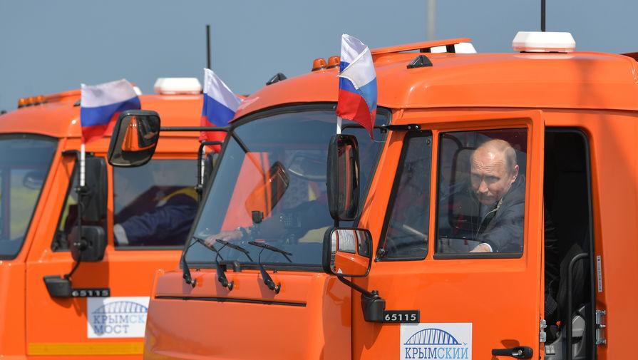 Президент России Владимир Путин садится за руль головной автомашины «Камаз» во время проезда колонны строительной техники по автодорожной части Крымского моста на торжественной церемонии открытия транспортного перехода, 15 мая 2018 года