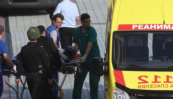 Транспортировка раненого к автомобилю скорой помощи после перестрелки в здании Мособлсуда, 1 августа 2017 года