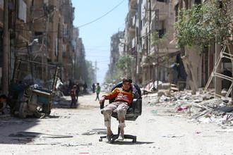 Мальчик сидит на одной из улиц города Дума, Сирия, 16 апреля 2018 года