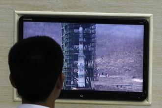 Работник северокорейского объекта, с которого будет запущен спутник, наблюдает за заливкой топлива в ракету-носитель.