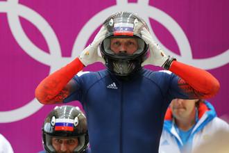 Александр Зубков (Россия) на старте в третьем заезде четверок на соревнованиях по бобслею среди мужчин