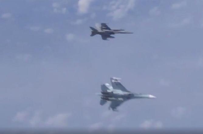 Российский Су-27 оттеснил истребитель НАТО F-18, который пытался приблизиться к самолету министра обороны Сергея Шойгу (кадр из видео)