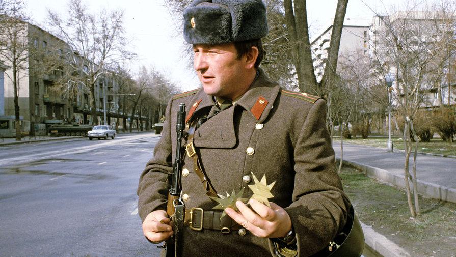 Офицер внутренних войск показывает предметы, которые использовали экстремисты в качестве метательного оружия, Душанбе, февраль 1990 года