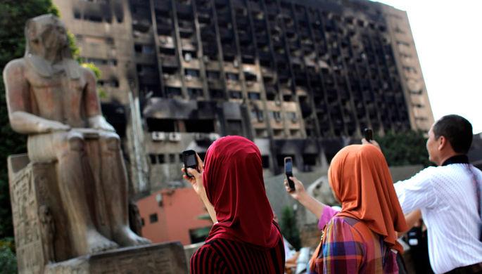 Туристы фотографируют статую перед Каирским музеем на фоне сгоревшего здания правящей партии Египта на площади Тахрир, 2011 год