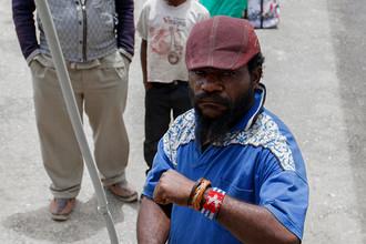 На руке символ «Papua Merdeka» — запрешённой в Индонезии сепаратистской организации, борющейся за отделение Западной Новой Гвинеи. За этот символ в Индонезии можно попасть в тюрьму.