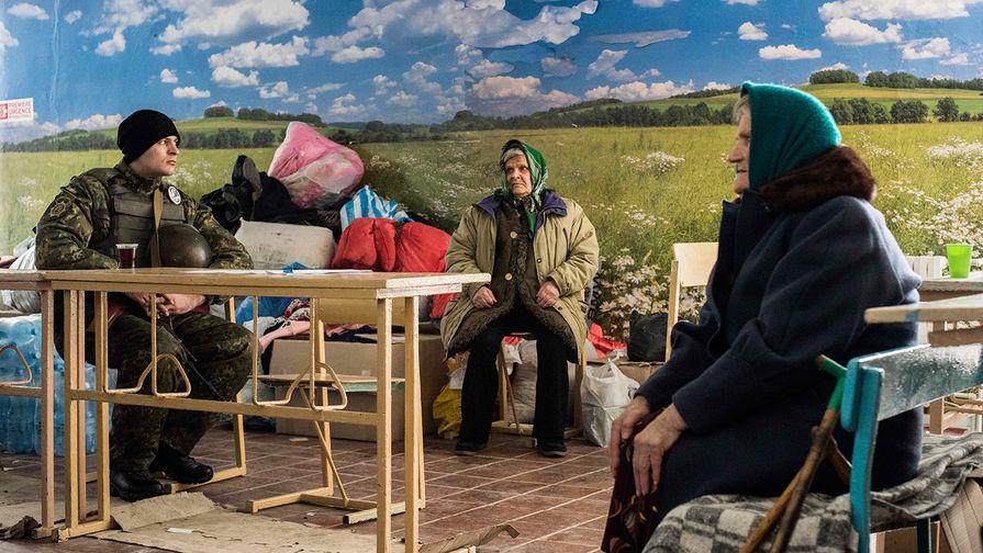 Украинский военнослужащий и пенсионеры в ожидании гуманитарной помощи в украинской Авдеевке, февраль...