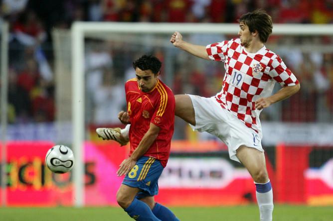 Хави ведет борьбу за мяч с Нико Кранчаром в матче Испания — Хорватия (2006)