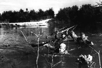 Бойцы подразделения гвардии старшего лейтенанта Енитского преодолевают водную преграду. Фото Наума Грановского. Фотография: репродукция фотохроники ТАСС