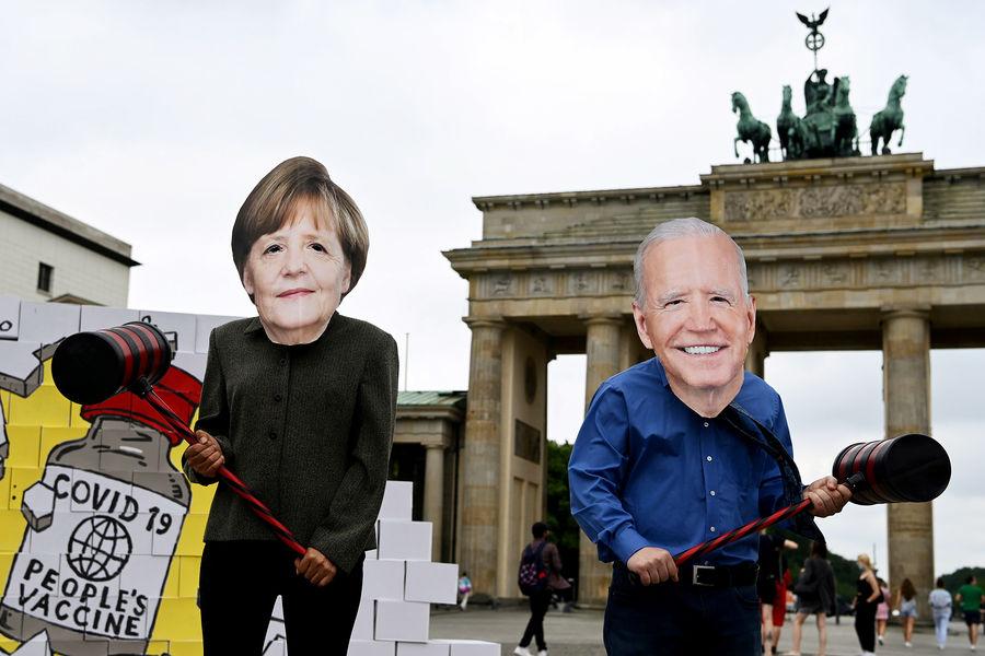 Протестующие в масках Меркель и Байдена в Берлине, 14 июля 2021 года
