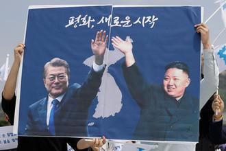 Активисты с портретами лидера Южной Кореи Мун Чжэ Ина и лидера Северной Кореи Ким Чен Ына в предверии саммита в Сеуле, 26 апреля 2018 года