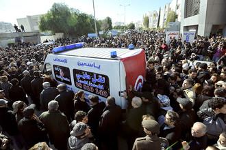 Автомобиль неотложной помощи с телом Чокри Белаида в окружении его сторонников