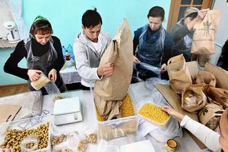 Волонтеры фасуют продукты в пакеты на складе гуманитарной помощи в рамках всероссийского благотворительного проекта для малоимущих