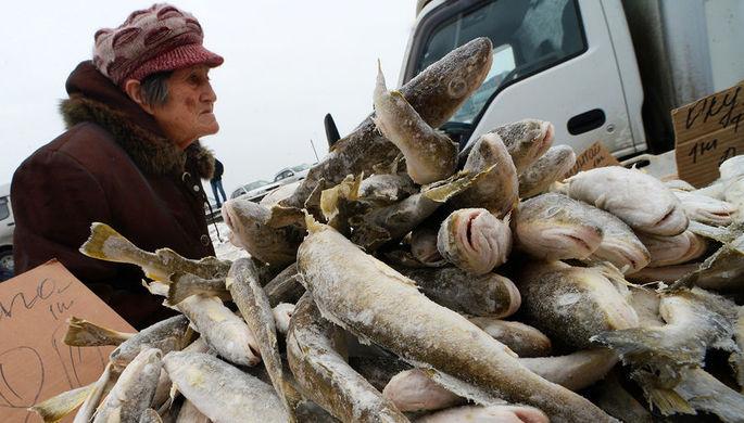 Посетитель у прилавка с рыбой на продовольственной ярмарке на центральной площади Владивостока