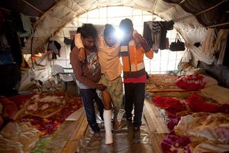 Рабочие из Бангладеш помогают раненому коллеге добраться до палатки