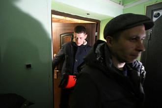 Трое следователей выходят из квартиры, где произошло преступление