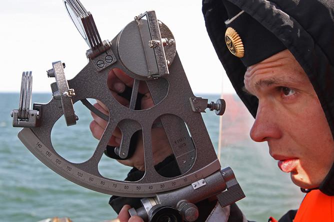 Моряк работает с секстантом на сторожевом корабле Балтийского флота РФ «Ярослав Мудрый» во время тактических учений