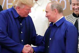 Президент США Дональд Трамп и президент России Владимир Путин пожимают руки во время встречи на саммите АТЭС во Вьетнаме, 10 ноября 2017 года