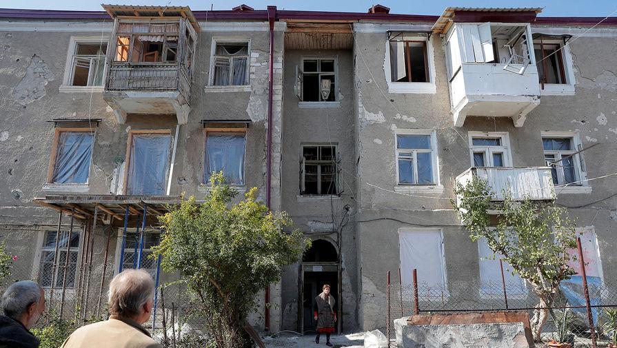 Поврежденный дом и местные жители в Степанакерте, 13 октября 2020 года