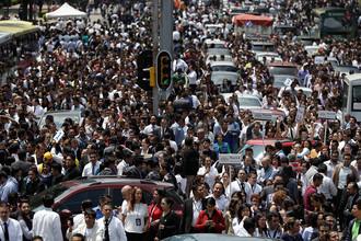 Эвакуированные из офисных зданий люди на главном проспекте Мехико после землетрясения в центральной части Мексики, 19 сентября 2017 года