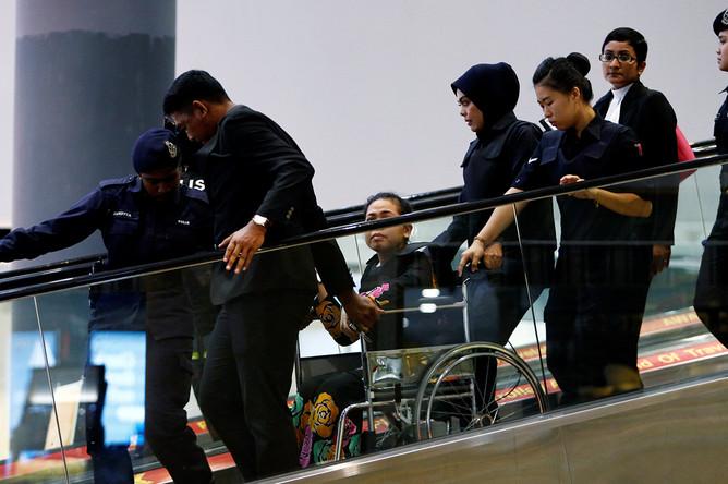 Подозреваемая в убийстве Ким Чон Нама гражданка Индонезии Сити Айсиа с полицейским сопровождением во время следственных действий в аэропорту Куала-Лумпура, 24 октября 2017 года