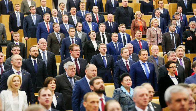 Депутаты во время исполнения государственного гимна на пленарном заседании Госдумы, декабрь 2017...