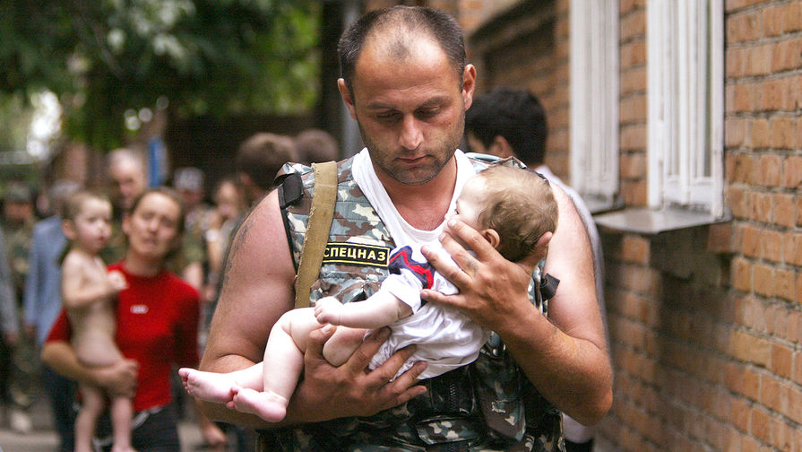 Сотрудник спецслужб выносит ребенка из захваченной террористами школы №1 в Беслане, 2 сентября 2004 года