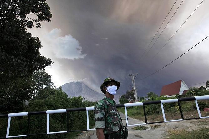 Индонезийская солдат на дороге, ведущей к Синабунгу, Северная Суматра, Индонезия