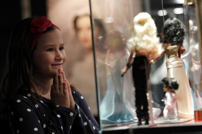 Девочка разглядывает кукол на выставке Барби в Загребе, май 2012 года