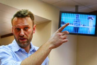 Алексей Навальный и его брат Олег Навальный (на экране по видеосвязи из СИЗО) перед рассмотрением жалобы защиты на приговор
