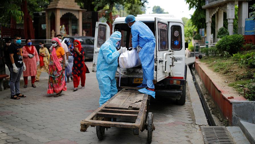Медики грузят в автомобиль тело умершего от коронавируса мужчины в Нью-Дели, сентябрь 2020 года