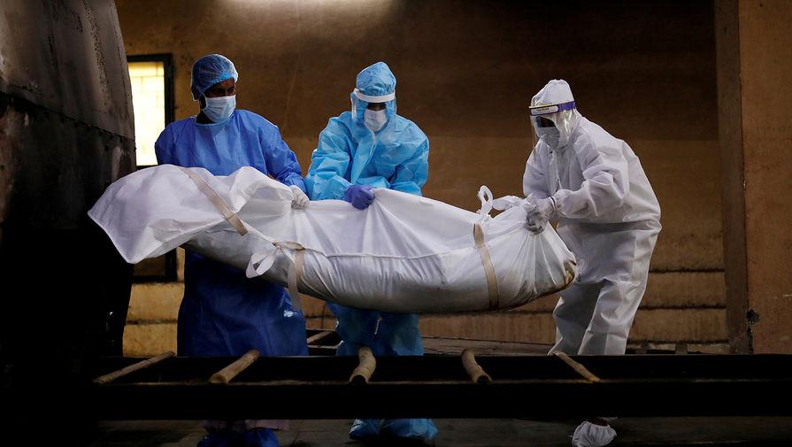 Сотрудники морга готовят к кремации тело умершего от коронавируса жителя Нью-Дели, сентябрь 2020 года