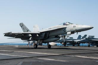 Американский палубный истребитель-бомбардировщик F/A-18E Super Hornet во время посадки на авианосец «Джордж Буш», после атаки по позициям террористической группировки «Исламское государство»