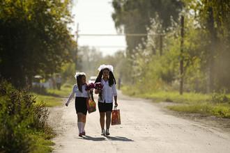 Дети идут в школу на торжественную линейку в селе Новолуговое Новосибирской области