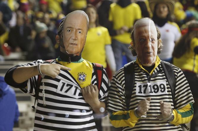 Бразильские болельщики в масках Йозефа Блаттера и экс-главы конфедерации футбола Бразилии Хосе Марии Марина